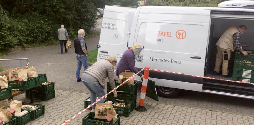Menschen mit gepackten Lebensmitteltüten vor einem Transporter